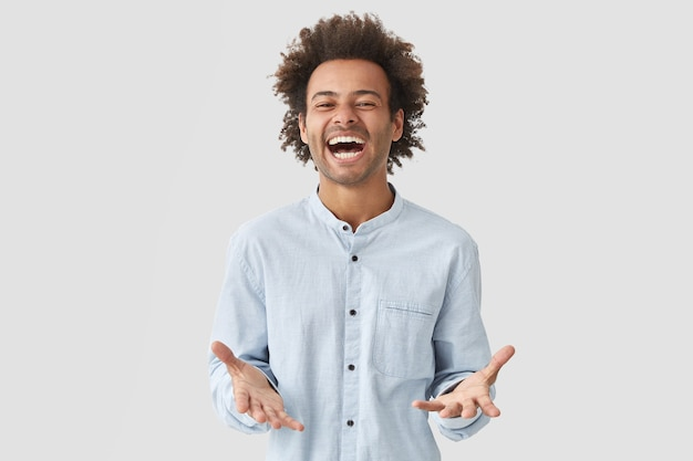 Overjoyed joyful attractive man student opens mouth widely, laughs joyfully, expresses positiveness, dressed in elegant shirt Free Photo