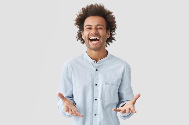 大喜びのうれしそうな魅力的な男の学生は、口を大きく開け、楽しく笑い、前向きさを表現し、エレガントなシャツを着ています 無料写真
