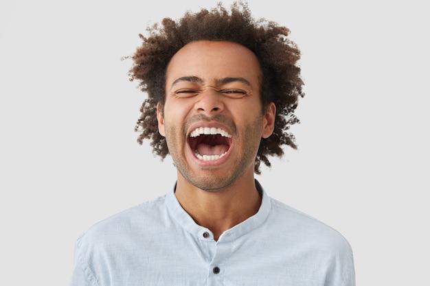 巻き毛の大喜びの男は、楽しく笑い、口を大きく開いたままにし、白い歯を見せます 無料写真