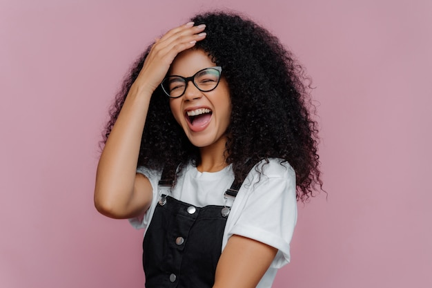 Overjoyed pleased curly haired woman keeps hand on forehead Premium Photo