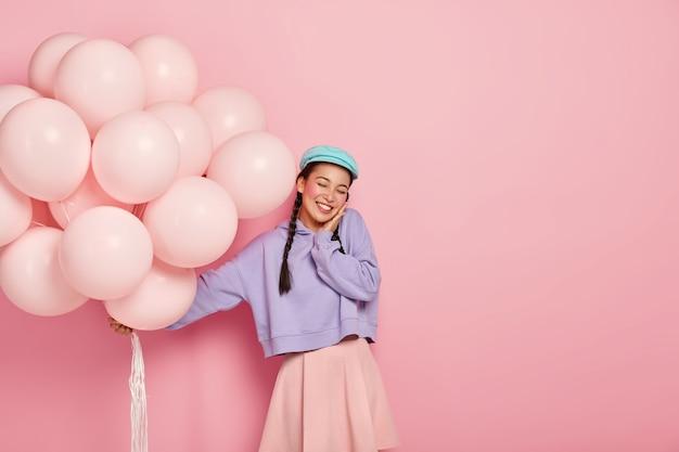 Una bella donna giapponese felicissima tiene gli occhi chiusi, si diverte a ricevere le congratulazioni per il successo dell'ingresso all'università, tiene i palloncini Foto Gratuite