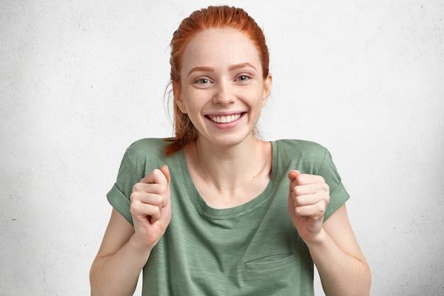 Обрадованная рыжая красивая счастливая молодая женщина празднует победу в конкурсе, одетая в повседневную футболку, с широкой улыбкой, изолированной на белом бетоне Бесплатные Фотографии