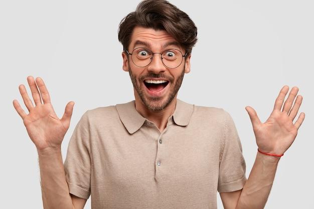 大喜びの無精ひげを生やした男は手を握りしめ、幸せな表情を持ち、白い壁に隔離されたカジュアルなtシャツを着て、親戚から受け取った良いニュースを喜ぶ 無料写真