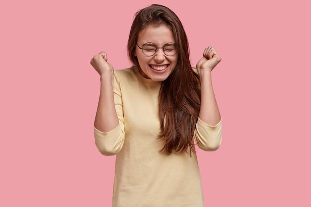 Обрадованная женщина поднимает сжатые кулаки в знак приветствия, наслаждается успехом и триумфом, носит очки и повседневную одежду, модели над розовым пространством Бесплатные Фотографии