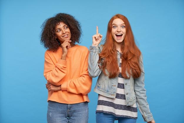 Обрадованная молодая красивая длинноволосая рыжая женщина поднимает указательный палец, взволнованно глядя, позируя над синей стеной с задумчивой позитивной кудрявой темнокожей брюнеткой Бесплатные Фотографии