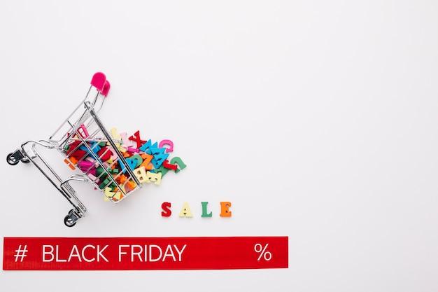 Overturned shopping cart with black friday ribbon Free Photo