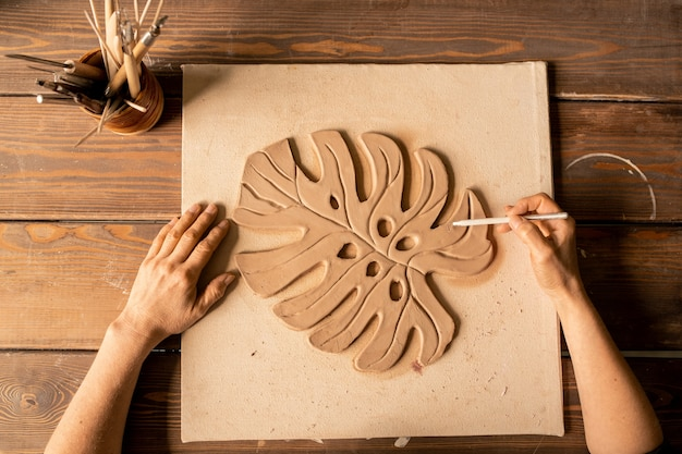 Overview of artist or carftsman with handtool working over clay item in form of palm leaf on wooden board Premium Photo