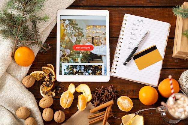 テーブル、クレジットカード、ペン、ギフトを購入する人々のリスト、クリスマスプロモーションのタブレットでのクリスマス用品の概要 Premium写真
