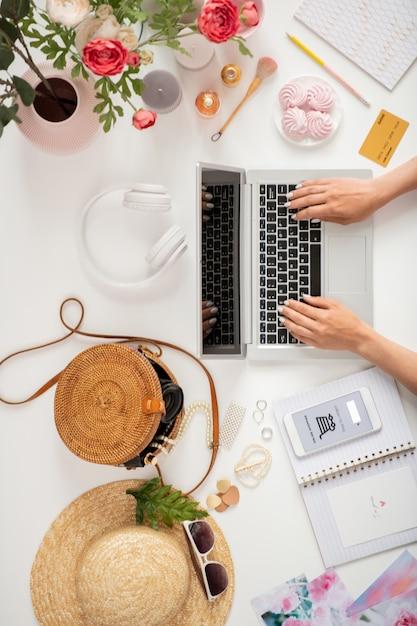 Обзор рук молодой женщины или деловой женщины на клавиатуре ноутбука в окружении различных предметов Premium Фотографии