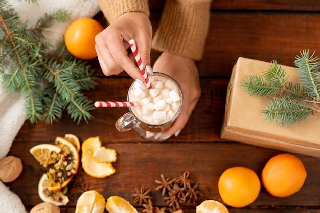 Обзор рук человека, держащего стакан латте с зефиром в окружении хвойных деревьев и свежих апельсинов Premium Фотографии
