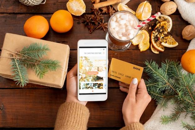 木製のテーブルの上のクリスマスオブジェクトに囲まれたスマートフォンとクレジットカードを使った人間の手の概要 Premium写真