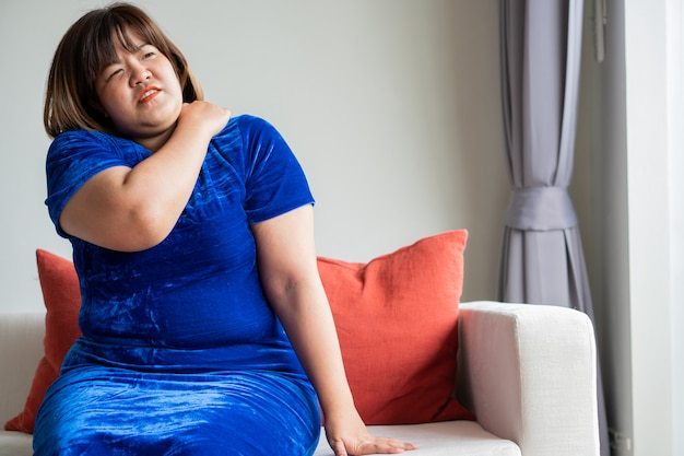 Overweight asian women sitting on the sofa in the living room. Premium Photo