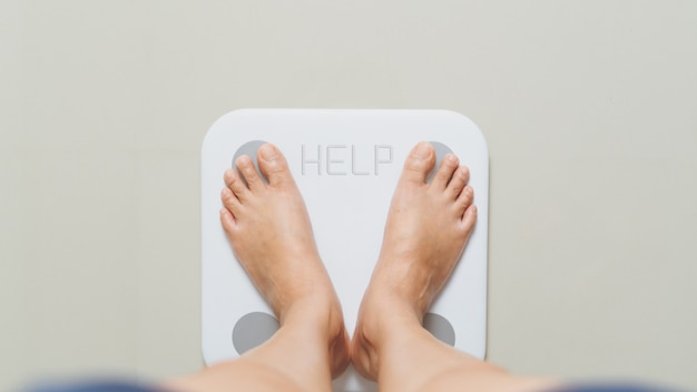 Overweight female is standing on white scales at home with help word Premium Photo