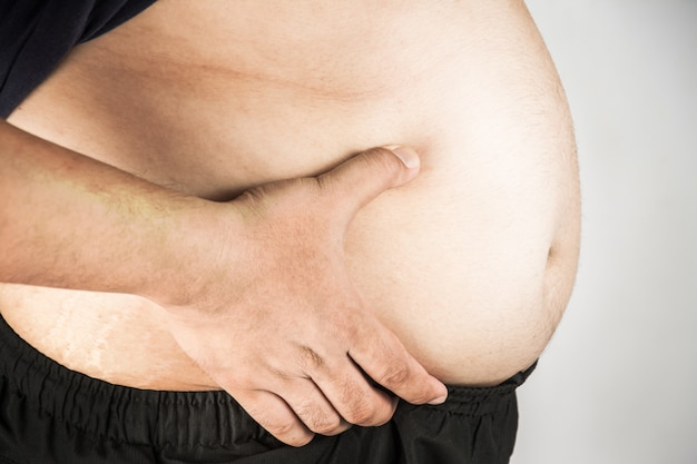 Overweight man body with hands touching belly fat Premium Photo