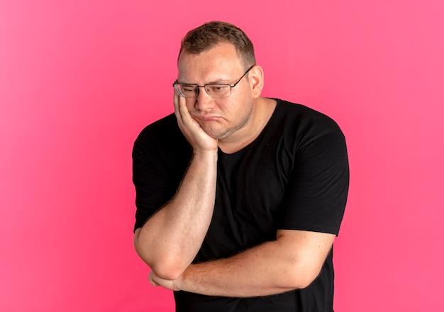 Uomo in sovrappeso con gli occhiali che indossa la maglietta nera infastidito appoggiando la testa sul braccio in attesa sul rosa Foto Gratuite