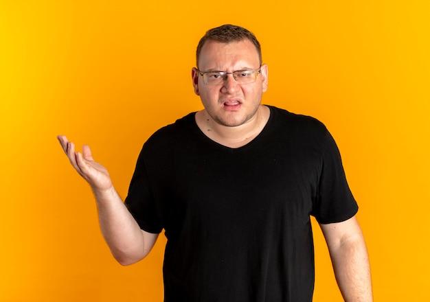 Uomo in sovrappeso con gli occhiali che indossa una maglietta nera scontento con il braccio in fuori come se chiedesse o discutesse sull'arancia Foto Gratuite