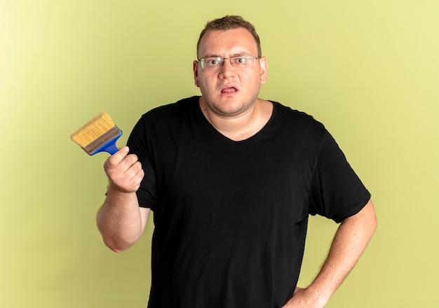 Uomo in sovrappeso con gli occhiali che indossa una maglietta nera che tiene il pennello come chiedere o discutere in piedi sopra la parete chiara Foto Gratuite