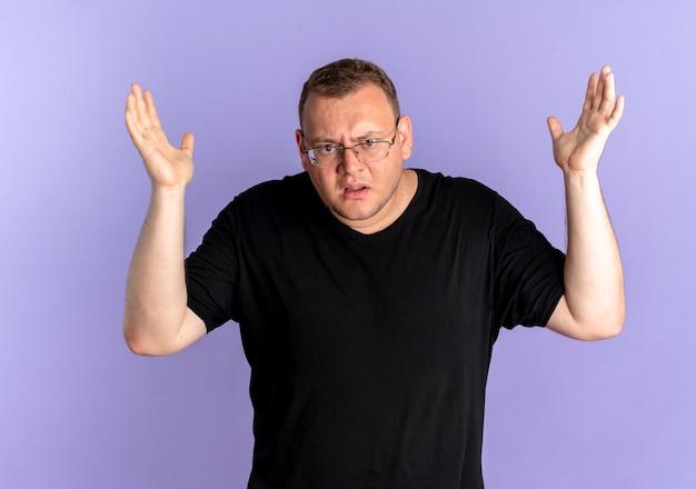 Uomo in sovrappeso con gli occhiali che indossa una maglietta nera che sembra confuso e scontento con le braccia alzate come chiedere o litigare in piedi sul muro blu Foto Gratuite