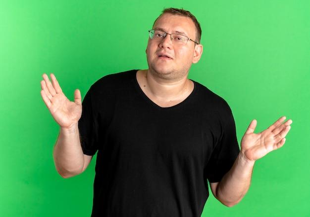Uomo in sovrappeso con gli occhiali che indossa una maglietta nera che sembra confuso e incerto allargando le braccia ai lati senza risposta sul verde Foto Gratuite