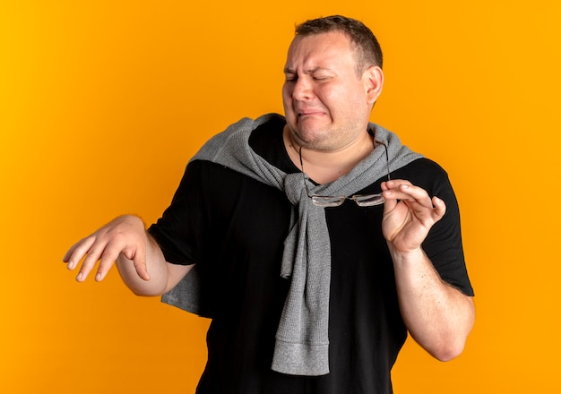 Overweight man in glasses wearing black t-shirt making defense gesture with hands with disgusted expression standing over orange wall Free Photo