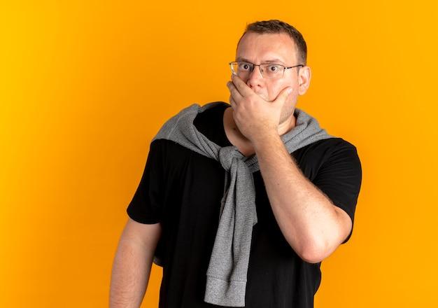 오렌지에 충격을 받고 손으로 입을 덮고 검은 티셔츠를 입고 안경에 과체중 남자 무료 사진