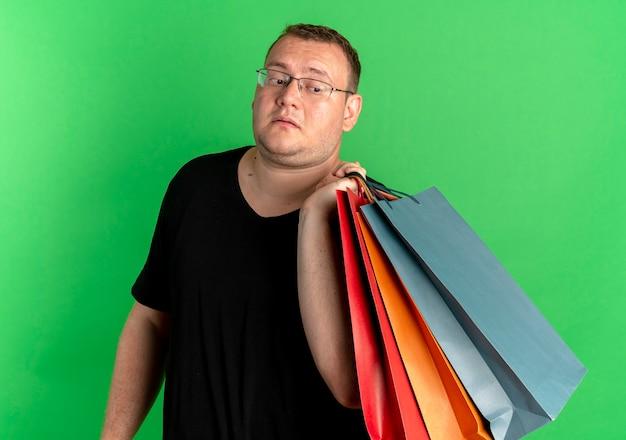 緑の上で混乱しているように見える紙袋を保持している黒いtシャツを着て眼鏡をかけた太りすぎの男 無料写真