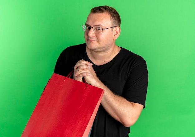 緑の壁の上に立って混乱しているように見える紙袋を保持している黒いtシャツを着て眼鏡をかけた太りすぎの男 無料写真