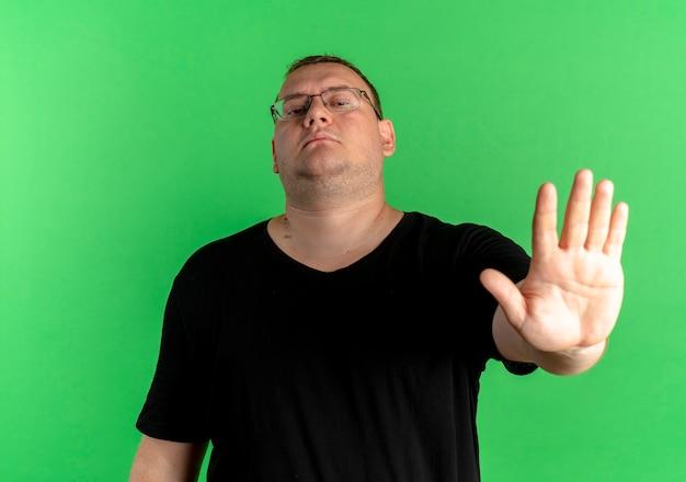 Полный мужчина в очках, одетый в черную футболку, заставляет прекратить петь с раскрытой ладонью с серьезным лицом, стоящим над зеленой стеной Бесплатные Фотографии