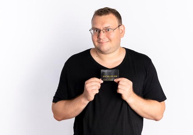 흰 벽 위에 서있는 행복한 얼굴로 카메라를보고 신용 카드를 보여주는 검은 티셔츠를 입고 안경에 과체중 남자 무료 사진