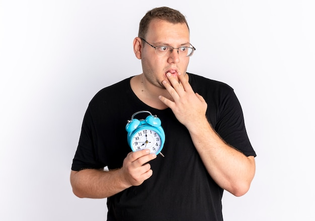 白い壁の上に立ってショックを受けている手で目覚まし時計を保持している眼鏡で黒いtシャツを着ている太りすぎの男 無料写真