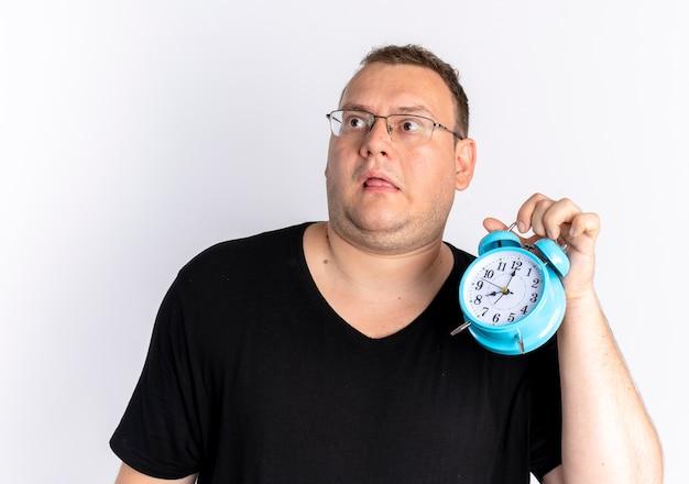 白い壁の上に立って混乱して目をそらしている目覚まし時計を保持している眼鏡で黒いtシャツを着ている太りすぎの男 無料写真
