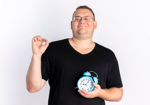 白い壁の上に立っている幸せそうな顔で笑顔で目覚まし時計を保持しているメガネで黒のtシャツを着ている太りすぎの男 無料写真