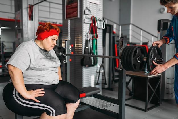 체육관에서 바벨 운동에 과체중 땀에 젖은 여자. 칼로리 연소, 스포츠 클럽에서 뚱뚱한 여성 사람 프리미엄 사진