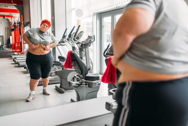 과체중 땀에 젖은 여자는 체육관에서 거울에 대한 그녀의 몸에 시계. 칼로리 연소, 스포츠 클럽에서 뚱뚱한 여성 사람 프리미엄 사진