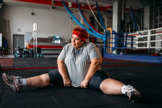 과체중 여성, 바닥에 운동, 체육관에서 운동. 칼로리 연소, 비만 여성, 스포츠 클럽 훈련 프리미엄 사진