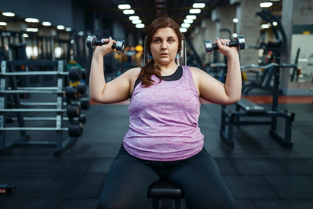 Overweight woman poses with dumbbells in gym, active training. Premium Photo