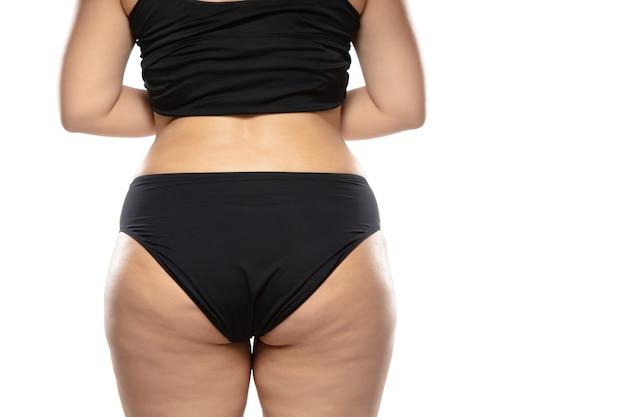 太ったセルライトの脚とお尻、黒い下着の肥満女性の体を持つ太りすぎの女性 無料写真