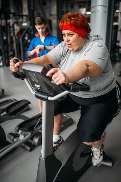과체중 여성, 체육관에서 운동 자전거 운동. 칼로리 연소, 스포츠 클럽의 비만 여성, 뚱뚱한 사람들 프리미엄 사진