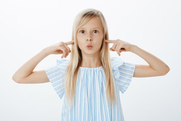 금발 머리를 가진 압도적 인 흥분된 귀여운 소녀, 접힌 입술로 삐걱 거리고 검지 손가락으로 귀를 덮고, 초점이 맞지 않고 지루하며 엄마와 쇼핑하는 동안 불순종 무료 사진