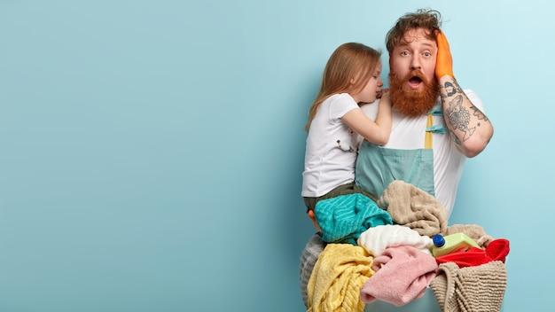L'uomo di zenzero barbuto e sorpreso sopraffatto tiene la mascella aperta, tiene la mano sulla testa, porta la figlia in lacrime, si sente perplesso, deve lavare il bucato, si trova contro il muro blu con uno spazio vuoto. Foto Gratuite