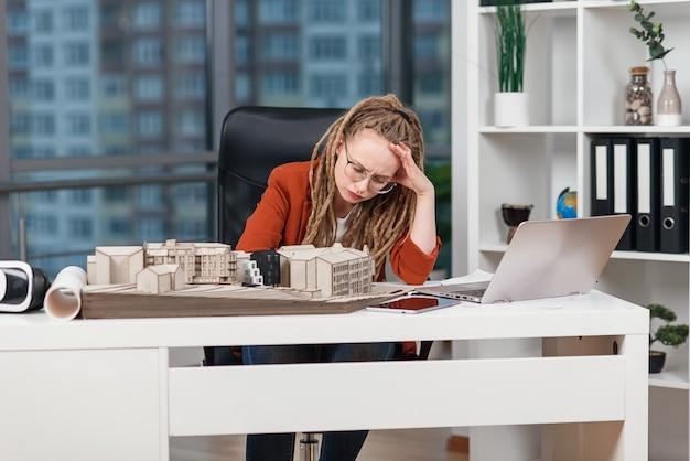Переутомленная деловая женщина испытывает стресс из-за каких-то проблем с архитектурным и дизайнерским проектом будущего здания. Premium Фотографии