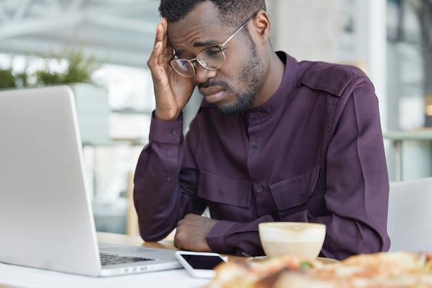 欲求不満な表情で働きすぎの疲れた暗い肌の男性、ラップトップの画面を必死に見て、ビジネスプロジェクトに取り組み、眠気を感じさせないようにコーヒーを飲みます。 無料写真