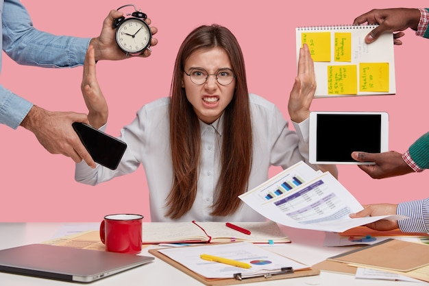 Overworked young employee refuses all things, frowns face in annoyance, sits at desktop with paper documents and notepad, isolated over pink wall. female worker bothered by many questions Free Photo