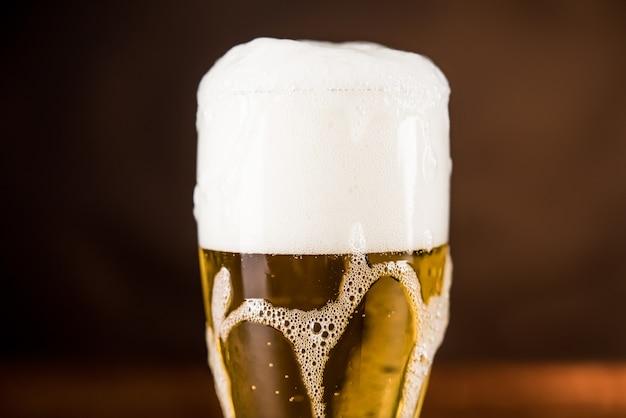 Холодное пиво в бокале на столе с пенистой пеной overyflow Premium Фотографии