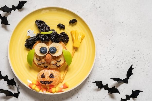 ハロウィーンの子供の朝食のための果物とフクロウのパンケーキ Premium写真