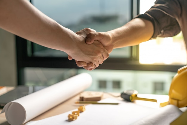 Owner and constructor  is agree and shake hands to celebrate in success of finish in contract home building construction project Premium Photo