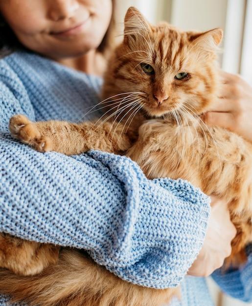 Proprietario che accarezza adorabile gatto Foto Gratuite