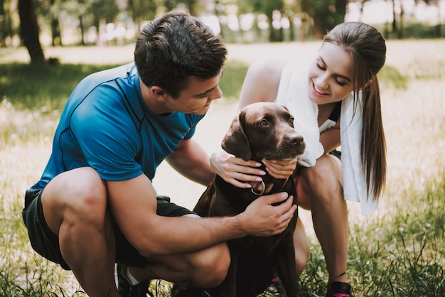 Owners is smiling and stroking their pet in green park Premium Photo