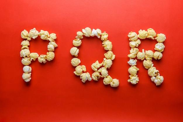 Попкорн, формирующий букву p, q, r на красном фоне Premium Фотографии
