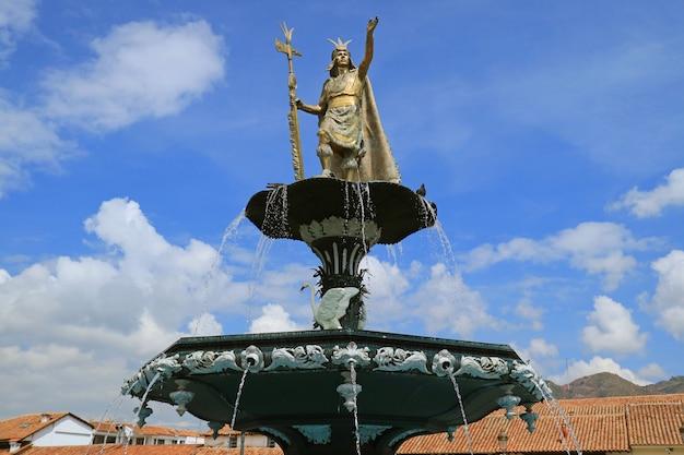 噴水、プラザデアルマス広場、クスコ、ペルーのpachacutiインカユパンキの像 Premium写真
